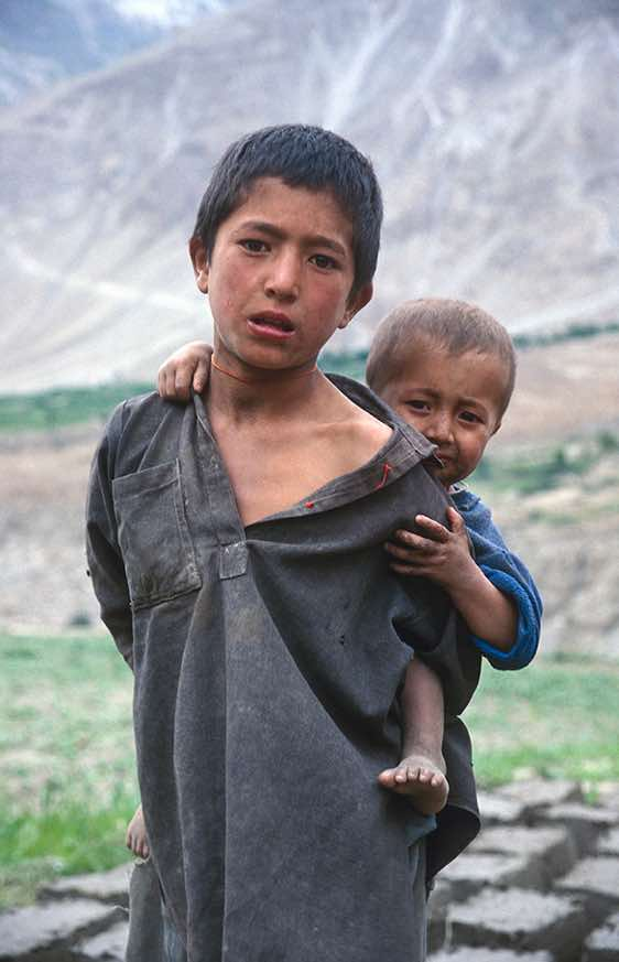 Boy enjoying a piggyback-ride, Askole, Karakoram Mountains