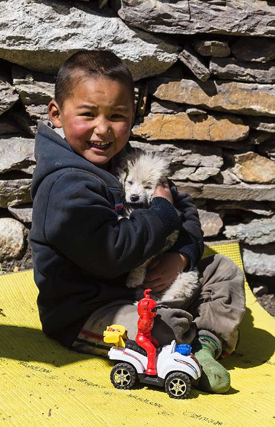 Boy with puppy dog, Sama (Samagaon), Buri Gandaki Valley, Around Manaslu Trek, Nepal Himalaya