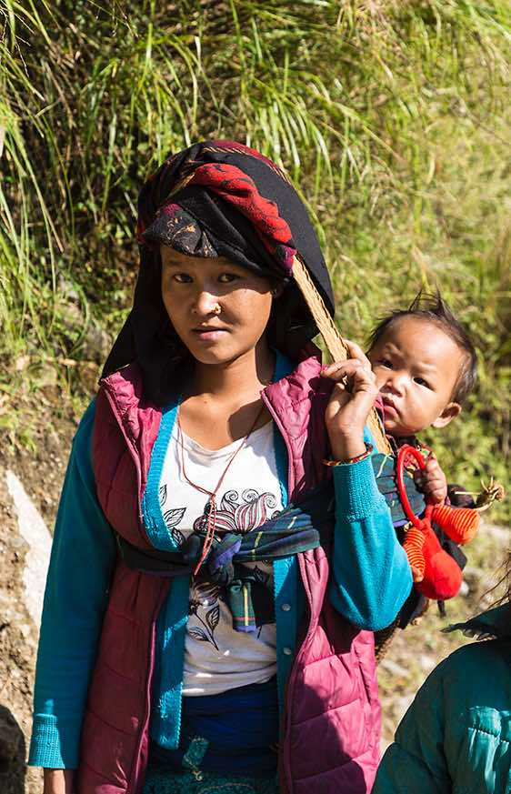 Boy enjoying a piggyback-ride, Buri Gandaki Valley, Around Manaslu Trek, Nepal Himalaya